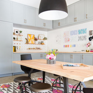 This is an example of an urban craft room in Seattle with white walls, a freestanding desk and grey floors.