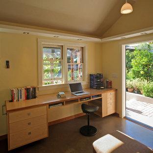 Imagen de despacho rural, pequeño, sin chimenea, con paredes amarillas, suelo de cemento y escritorio empotrado