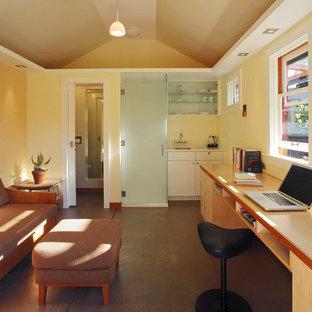 Ispirazione per un grande studio contemporaneo con pareti gialle, pavimento in cemento, nessun camino e scrivania incassata