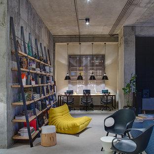 Foto på ett industriellt hemmabibliotek, med grå väggar och ett fristående skrivbord