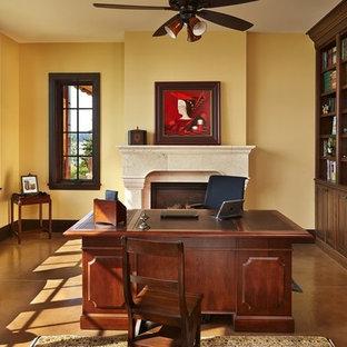 シアトルの大きいトラディショナルスタイルのおしゃれなホームオフィス・仕事部屋 (黄色い壁、標準型暖炉、石材の暖炉まわり、自立型机) の写真