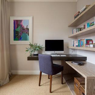 Inspiration för små klassiska hemmabibliotek, med beige väggar, ett inbyggt skrivbord, beiget golv och heltäckningsmatta