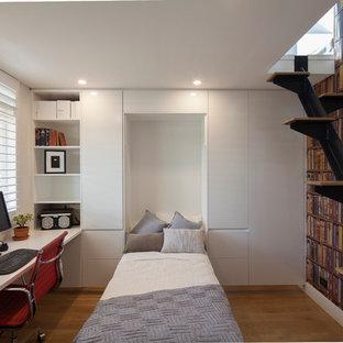 Réalisation d'un petit bureau minimaliste avec un bureau intégré, un mur blanc, un sol en bois brun et aucune cheminée.