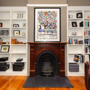 シドニーの広いヴィクトリアン調のおしゃれな書斎 (グレーの壁、淡色無垢フローリング、標準型暖炉、木材の暖炉まわり、自立型机) の写真