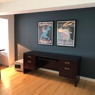 Esempio di un ampio studio contemporaneo con pareti blu, pavimento in bambù, scrivania autoportante e pavimento marrone