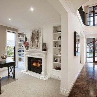 Idee per un ampio studio classico con pareti bianche, pavimento in legno massello medio, camino classico, cornice del camino in pietra e scrivania autoportante