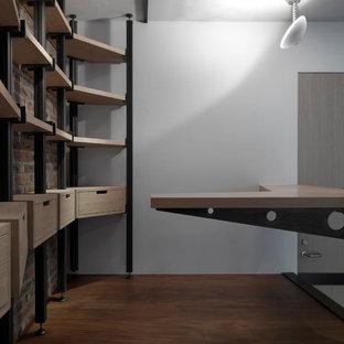Idée de décoration pour un petit bureau urbain avec un mur marron, un sol en bois brun, un bureau intégré et un sol marron.