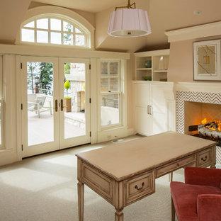 ミネアポリスのビーチスタイルのおしゃれな書斎 (ベージュの壁、カーペット敷き、標準型暖炉、タイルの暖炉まわり、自立型机、ベージュの床) の写真