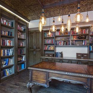 Ispirazione per uno studio mediterraneo con libreria, pareti bianche, parquet scuro, scrivania autoportante e pavimento marrone