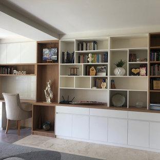 Foto di un grande studio minimal con libreria, pareti bianche, pavimento in travertino, scrivania incassata e pavimento beige