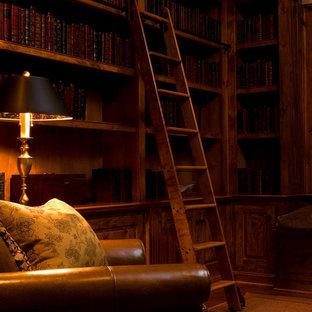 Immagine di uno studio american style di medie dimensioni con libreria, pareti beige e pavimento in legno massello medio