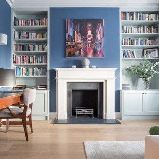 Idee per un ufficio bohémian di medie dimensioni con pareti blu, parquet chiaro, camino classico, cornice del camino in pietra, scrivania autoportante e pavimento beige