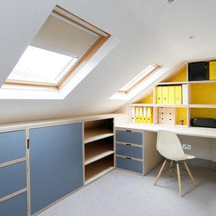 Idee per uno studio design con pareti gialle, scrivania incassata e pavimento grigio