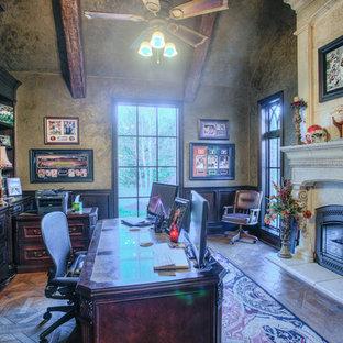 Immagine di un grande ufficio stile rurale con pareti grigie, pavimento in legno massello medio, camino classico, cornice del camino in cemento, scrivania autoportante e pavimento marrone