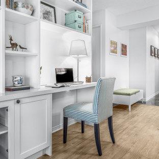 トロントの中くらいのトランジショナルスタイルのおしゃれな書斎 (白い壁、磁器タイルの床、造り付け机、ベージュの床) の写真