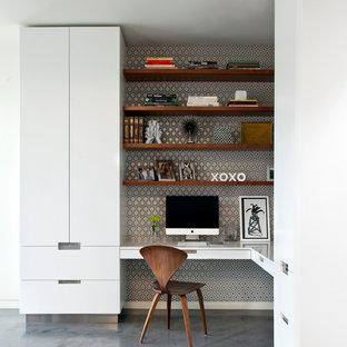 На фото: рабочее место в современном стиле с бетонным полом, встроенным рабочим столом и разноцветными стенами