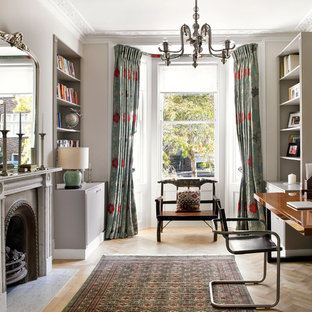 Ornate freestanding desk medium tone wood floor study room photo in London with gray walls and a standard fireplace