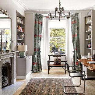 ロンドンのヴィクトリアン調のおしゃれな書斎 (グレーの壁、無垢フローリング、標準型暖炉、自立型机) の写真