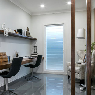 Inspiration for a mid-sized transitional study room in Other with white walls, a built-in desk and grey floor.