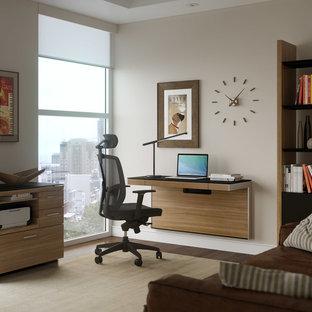 Example of a trendy built-in desk dark wood floor home office design in DC Metro with beige walls