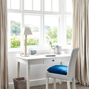 This is an example of a coastal study in Wiltshire with white walls, carpet, a freestanding desk and beige floors.