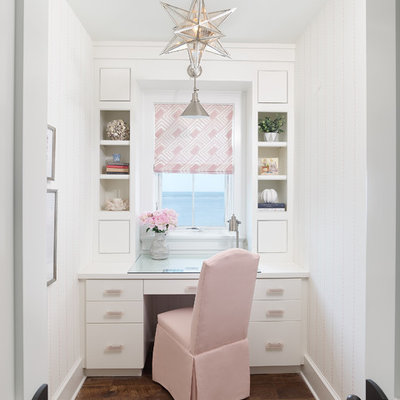 Example of a beach style built-in desk dark wood floor and brown floor home office design in Charleston with white walls