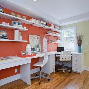 サンフランシスコのビーチスタイルのおしゃれなホームオフィス・書斎 (オレンジの壁、無垢フローリング、造り付け机) の写真