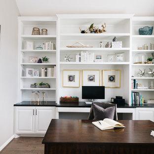 Inspiration för ett maritimt hemmabibliotek, med grå väggar, mörkt trägolv, ett fristående skrivbord och brunt golv