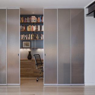 Modelo de despacho minimalista con paredes grises y suelo de madera clara