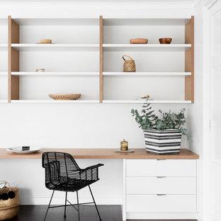 Aménagement d'un bureau scandinave de taille moyenne avec un mur blanc, un sol en bois foncé et un bureau intégré.