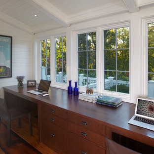 Example of a mid-sized transitional built-in desk medium tone wood floor home office design in New York with white walls and no fireplace
