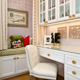 Inredning av ett klassiskt arbetsrum, med lila väggar, mellanmörkt trägolv och ett inbyggt skrivbord