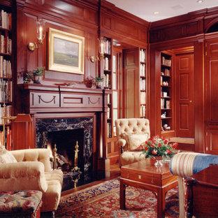 Esempio di uno studio tradizionale di medie dimensioni con libreria, parquet scuro, camino classico, cornice del camino in pietra, pareti marroni e pavimento marrone