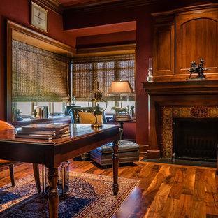 ヒューストンの大きいラスティックスタイルのおしゃれな書斎 (赤い壁、無垢フローリング、両方向型暖炉、木材の暖炉まわり、自立型机、茶色い床) の写真