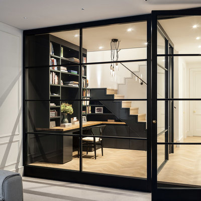 Study room - small contemporary built-in desk light wood floor study room idea in London with black walls