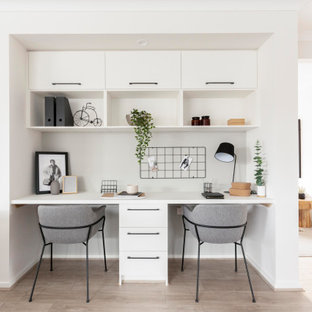 Inredning av ett industriellt hemmabibliotek, med vita väggar, laminatgolv, ett inbyggt skrivbord och beiget golv