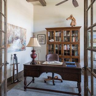 Tuscan freestanding desk dark wood floor and brown floor study room photo in Austin with beige walls