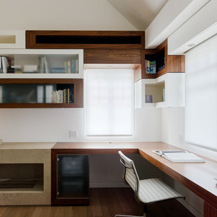Trendy built-in desk light wood floor and brown floor study room photo in San Francisco with white walls