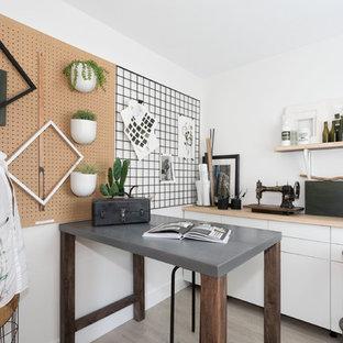 Imagen de sala de manualidades actual, pequeña, con paredes blancas, suelo laminado, escritorio empotrado y suelo beige