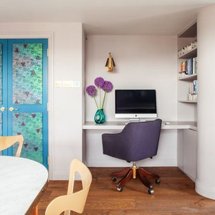 Design ideas for a small traditional home office and library in London with a built-in desk, brown floors, white walls and medium hardwood flooring.