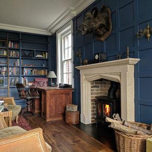 Inspiration för mellanstora klassiska hemmabibliotek, med blå väggar, mellanmörkt trägolv, en öppen vedspis, ett fristående skrivbord, brunt golv och en spiselkrans i tegelsten