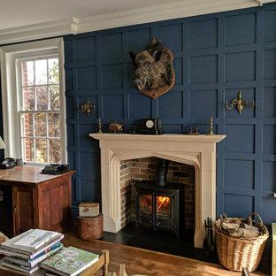 Immagine di un ufficio tradizionale di medie dimensioni con pareti blu, pavimento in legno massello medio, stufa a legna, cornice del camino in pietra, scrivania autoportante e pavimento marrone