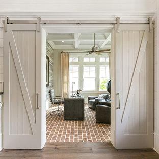Inspiration för maritima arbetsrum, med vita väggar, tegelgolv, ett fristående skrivbord och rött golv
