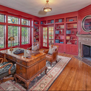 Foto di un grande studio tradizionale con pareti rosse, pavimento in legno massello medio, camino ad angolo, cornice del camino in pietra, scrivania autoportante e pavimento marrone