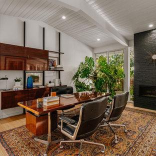 Inspiration för mellanstora retro arbetsrum, med ljust trägolv, en bred öppen spis, en spiselkrans i tegelsten och ett fristående skrivbord
