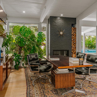 Foto på ett mellanstort 60 tals arbetsrum, med ljust trägolv, en bred öppen spis, en spiselkrans i tegelsten, ett fristående skrivbord, vita väggar och beiget golv