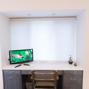 ボストンの中くらいのモダンスタイルのおしゃれなホームオフィス・書斎 (白い壁、スレートの床、造り付け机、黒い床) の写真