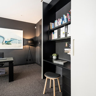 This is an example of a small modern study room in Melbourne with black walls, carpet, a built-in desk and grey floor.