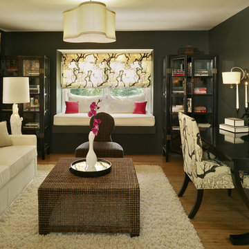 Black walls become cozy when accented with white upholstery in this study