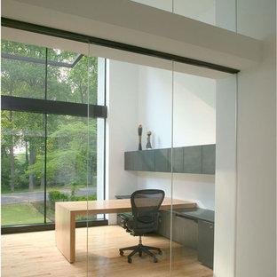 Exemple d'un bureau moderne de taille moyenne avec un mur blanc, un sol en bois clair et un bureau intégré.